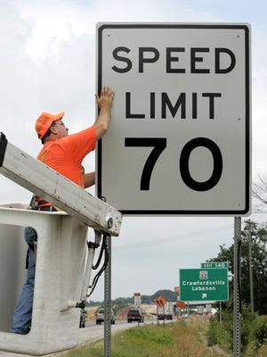 A 2005 photo shows an Indiana Department of Transportation worker installing a 70 mph speed limit sign along an interstate. Pennsylvania increased the speed limit on some stretches of highway to 70 mph in 2014, and is now expanding the new limit to more roads.