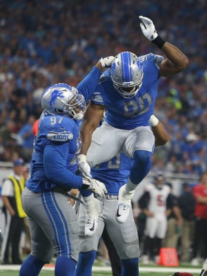 Cornelius Washington (90) and Akeem Spence (97) celebrate a defensive play in the third quarter of the Lions' 30-26 loss to the Falcons, Sunday, Sept. 24, 2017 at Ford Field.
