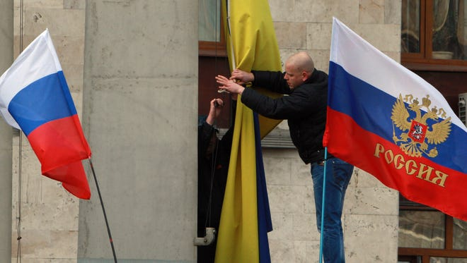 Pro-Russian activists remove the Ukrainian flag, center, to replace it with a Russian one on an administration office in the center of Donetsk, Ukraine, Saturday, March 1, 2014. Supporters of new Ukrainian authorities and pro-Russia demonstrators clashed in Kharkiv and Donetsk a mostly Russian-speaking region in eastern Ukraine. (AP Photo/Sergey Vaganov)