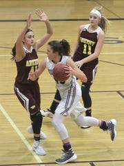 Indianola sophomore Grace Berg drives past Ankeny senior Hannah Shadravan and junior Codee Myers. Class 5-A fifth-ranked Indianola beat Ankeny 52-47 in Indianola on Dec. 15.