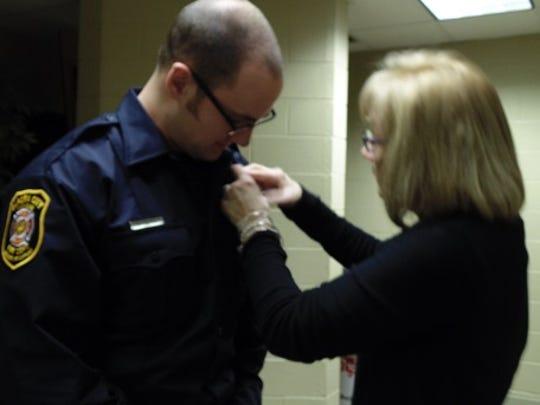 Kody Gazdag receives his new badge from mom Lynn Gazdag.