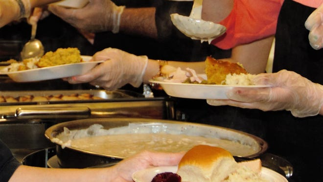 Handing off plates of food at a Thanksgiving Day meal served at Howard Payne University.