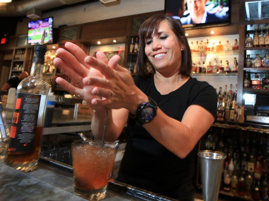 Doc Crow bartender Keri Smith mixes drinks at the downtown eatery and bar.