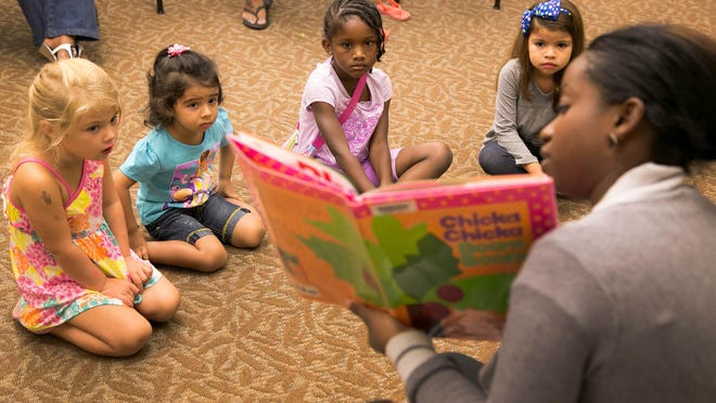 Children listen to Keisha Crooks read a book during children's story time at the Palm Beach County library on Summit Boulevard in West Palm Beach, Florida on July 1, 2014.