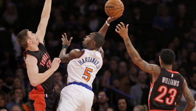 New York Knicks' Tim Hardaway Jr., center, shoots past Toronto Raptors' Tyler Hansbrough, left, and Louis Williams during the first half of an NBA basketball game, Sunday, Dec. 14, 2014 in New York.