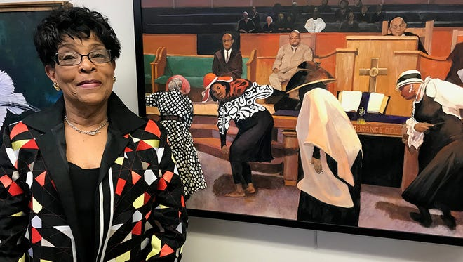 Donna Kennedy with her painting, which is on display at the Detroit Public Library through May 26.