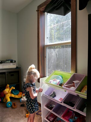 Sophie Sherman, 3, plays with her toys by a second-story window of her Seabeck home. She fell out of the window last summer after leaning against the screen. She suffered only minor injuries, and now her family is raising awareness about how easy it is for kids to fall out of windows.