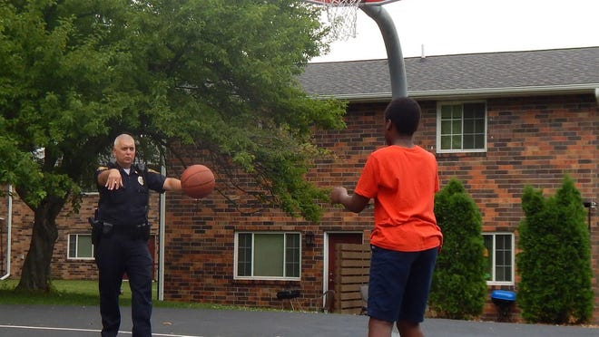 Burlington Police Major Adam Schaefer plays a little one-on-one with Jaharri Collins, 9, of Burlington Sunday at DeEdwin and Gladys White Memorial Park in Burlington during this year's annual Juneteenth celebration. More than 100 people gathered at the park on Angular Street to enjoy a DJ, free food, games and prizes.