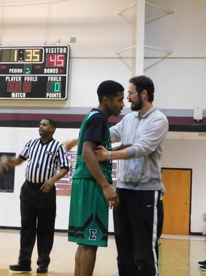 Eunice High boys' basketball coach Chad Andrepont congratulates a player who returns to the Bobcats' bench during Wednesday's game with East Iberville.
