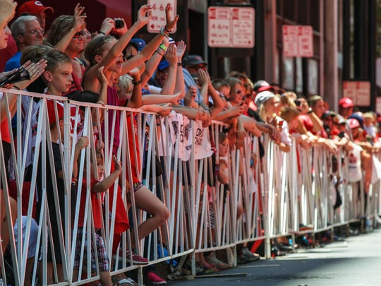 Parade watchers wave to players of the 2015 All-Star Leagues as they ride the streets of Downtown along a red carpet during the 11th annual MLB All-Star Red Carpet Show Tuesday.