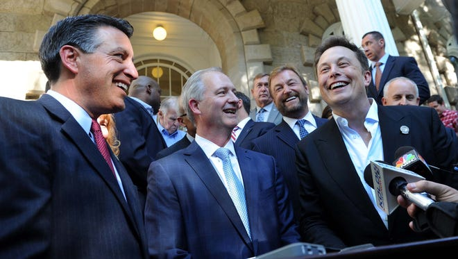 Gov. Brian Sandoval, left, and Elon Musk, chairman and CEO of Tesla, right, in Carson City in 2014.