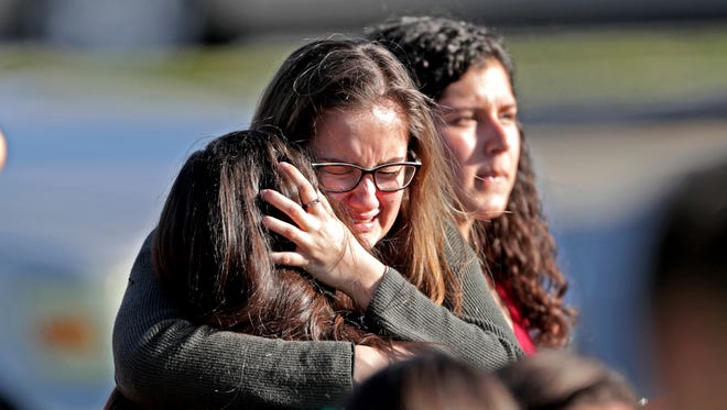 Students released from a lockdown embrace following following a shooting at Marjory Stoneman Douglas High School.