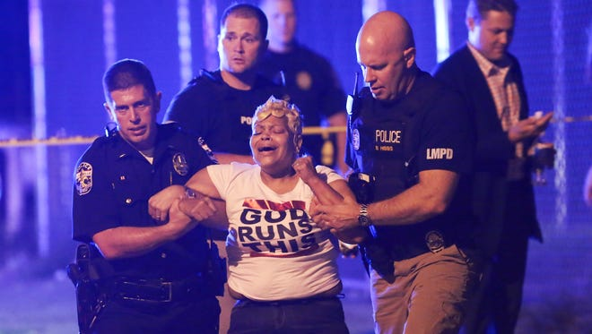 LMPD officers assisted a distraught woman who arrived at the scene of a multiple shooting near Clay and Jacob streets in Smoketown.Aug. 24, 2016