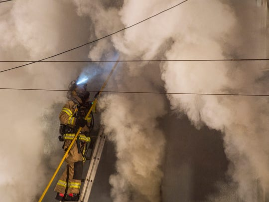 A firefighter engulfed in smoke breaks out windows at the former Mane Street Hair and Tanning Salon as an estimated 50 or more firefighters battled a two-alarm fire at the former First National Bank of Fredericksburg at the corner of Pine Grove and Main streets in Fredericksburg on Tuesday, Dec. 20, 2016.