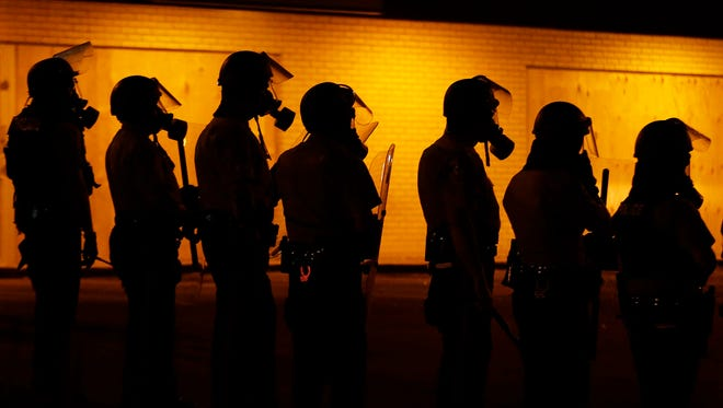 FILE - In this Sunday, Aug. 17, 2014, file photo, police wait to advance after tear gas was used to disperse a crowd during a protest for Michael Brown in Ferguson, Mo. Missouri and St. Louis-area economic development groups and lenders are committing $1 million in support to businesses affected by the unrest in Ferguson that followed the shooting death of an unarmed black 18-year-old by a white police officer, Gov. Jay Nixon said Thursday, Aug. 28, 2014. (AP Photo/Charlie Riedel, File)