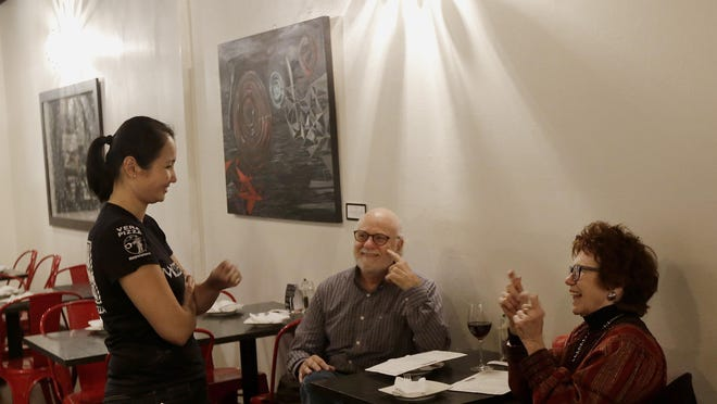 Mozzeria owner Melody Stein, left, communicates with customers Ronald Ransom and Betty Ann Prinz using sign language in San Francisco. Mozzeria owners Russ and Melody Stein as well as staff workers are deaf and have run their San Francisco restaurant since 2011.