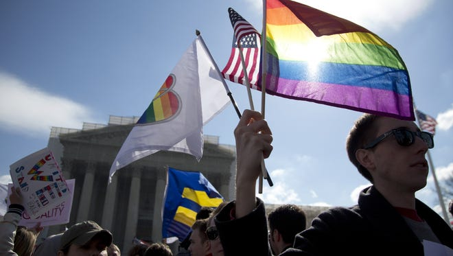 Kevin Coyne of Washington holds flags in front of the Supreme Court in March as the court hears arguments on gay marriage.