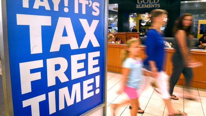 Customers pass by signs at Opry Mills Mall advertising tax-free weekend sales Friday, July 29, 2016.