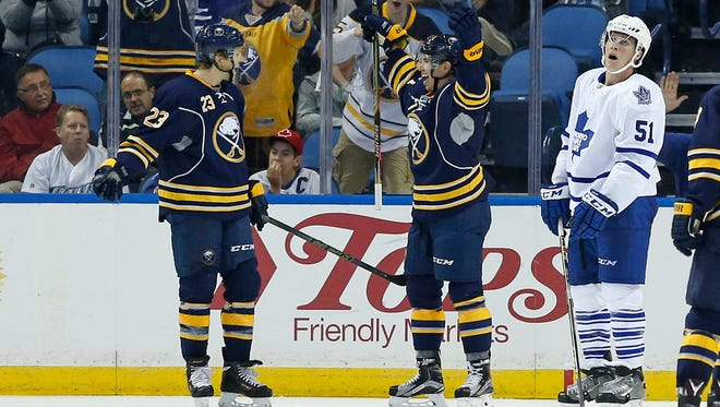 Evan Rodrigues celebrates with Sam Reinhart (23) after scoring against Toronto on Tuesday, much to the dismay of Leafs defenseman Jake Gardiner. Rodrigues was assigned to the Amerks on Friday.