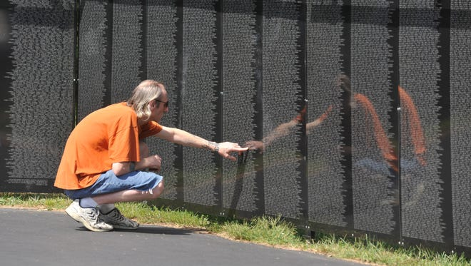Bryan Green touches the name of his father, Willard Downing, on The Wall That Heals in the Veterans Memorial Park in Richmond on Aug. 26, 2011.