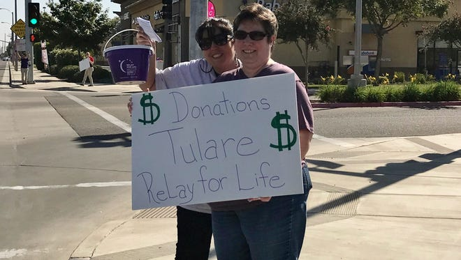 Kristy Fagundes, left, and Laura Hernandez stand on a Tulare corner asking for Relay for Life donations.