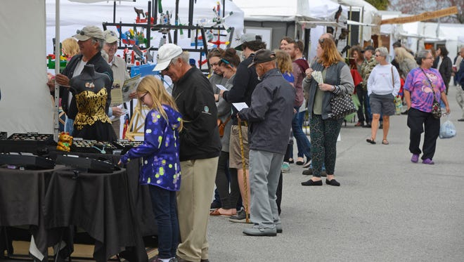 Visitors check out art for sale Sunday during the 23rd annual Gulf Breeze Celebrates the Arts fine arts festival at Gulf Breeze High School.