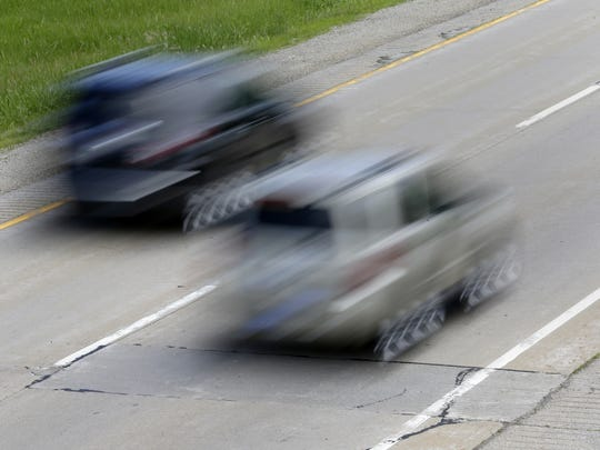 Vehicles drive past a patched piece of road on State 441 while heading to Calumet Street on June 23 in Appleton.