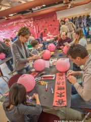 Families work on Chinese lanterns during a Family Explorers