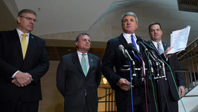 House Homeland Security Committee Chairman Rep. Michael McCaul, R-Texas, second from right, standing with, from left, Rep. Barry Loudermilk, R-Ga., Rep. Buddy Carter, R-Ga., and Rep. Richard Hudson, R-N.C., speaks to reporters on Capitol Hill in Washington on Friday about the arrest of two Iraqi-born men who came to the United States as refugees and were indicted on terrorism-related charges by federal authorities. McCaul holds a copy of one of the indictments.