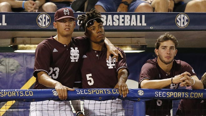 Mississippi State's Austin Sexton, left, and Mike Smith, right, hug in the dugout during the inning third inning of a Southeastern Conference NCAA college baseball tournament game at the Hoover Met, Thursday, May 26, 2016, in Hoover, Ala. LSU won 6-2.