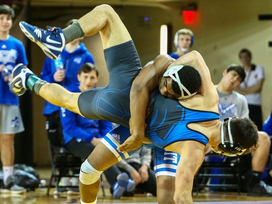 Catholic Central's Josh Edmond (top) takes down his