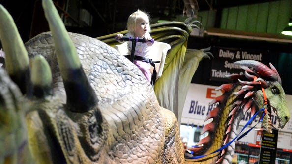 Catherine Smith, 2, of Harrisonburg rides a dinosaur during the Dinosauria Experience at Expoland in Fishersville on Sunday, June 22, 2014.