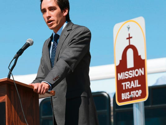 VICTOR CALZADA-EL PASO TIMES County Commissioner Vince Perez talks about the new Mission Trail Express bus route Wednesday during a press conference. The sign for the the bus route is at right.