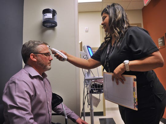 Olney Hamilton Hospital LVN Angela Moreno takes the vital signs of John Ingle, business editor for the Wichita Falls Times Record News, for a story on DNA sampling and genetic testing for prescribing more effective medications and dosages.