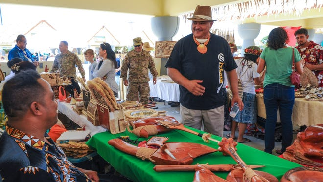 Visitors check out the various points of interest during the Festival of Pacific Arts at the Paseo in Hagatna on Thursday, May 26.