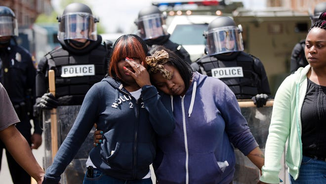 "Two sisters embrace as people sing ""Amazing Grace"" Baltimore, in the aftermath of rioting following funeral services for Freddie Gray."
