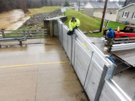 Workers reach to place a piece of the flood gate in