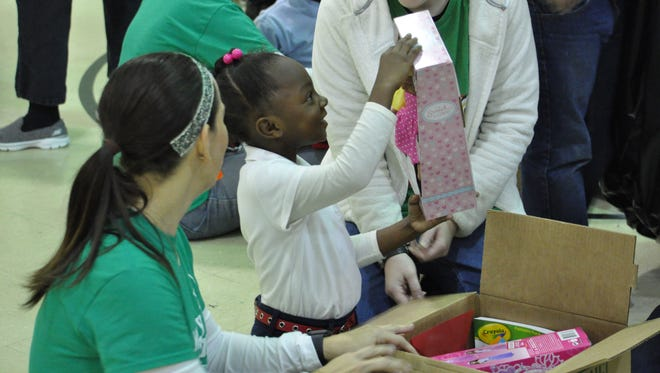 Calvary Baptist Church members help Julius Patrick students unwrap gifts donated by the church on Tuesday.