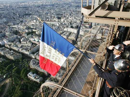 Paris, FRANCE:  Paris Firemen display a French national flag on the balcony of the Eiffel tower 25 August 2004 in Paris in memory of their 1944 colleagues who did it on the day when Paris was liberated from Nazi occupation. Paris on 25 August was set to celebrate the 60th anniversary of its liberation from Nazi occupation with a day of military parades and solemn ceremonies culminating in a festive 1940s dance party. AFP PHOTO PIERRE VERDY  (Photo credit should read PIERRE VERDY/AFP/Getty Images)
