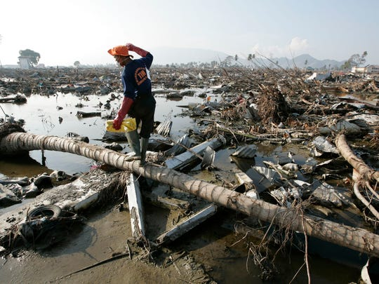 Dec. 25, 2004: 230,000 dead in Indonesia. Search-and-rescue team member Ngatno carefully walks across debris in the hard hit area of Banda Aceh known as Punge on Jan. 20, 2005.