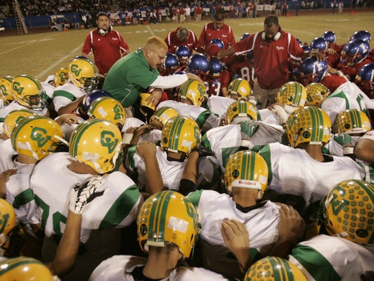"""Coachella Valley HIgh School and Indio High School football players pray together prior to the start of their """"Victory Bell"""" match at Indio High School."""