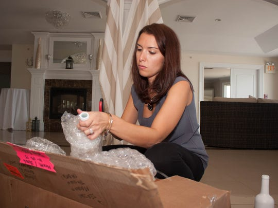 Event planner Mallory Rapisarda unpacks and organizes wedding decorations for a reception at Windows on the Water in Sea Bright.