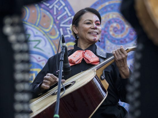 Betty Duarte-Matwick of the all-female Mariachi band, Mariachi Pasion, plays guitar during the group's performance at the Dia De Los Muertos Celebration at the Desert Botanical Garden in Phoenix, Nov. 2, 2014.