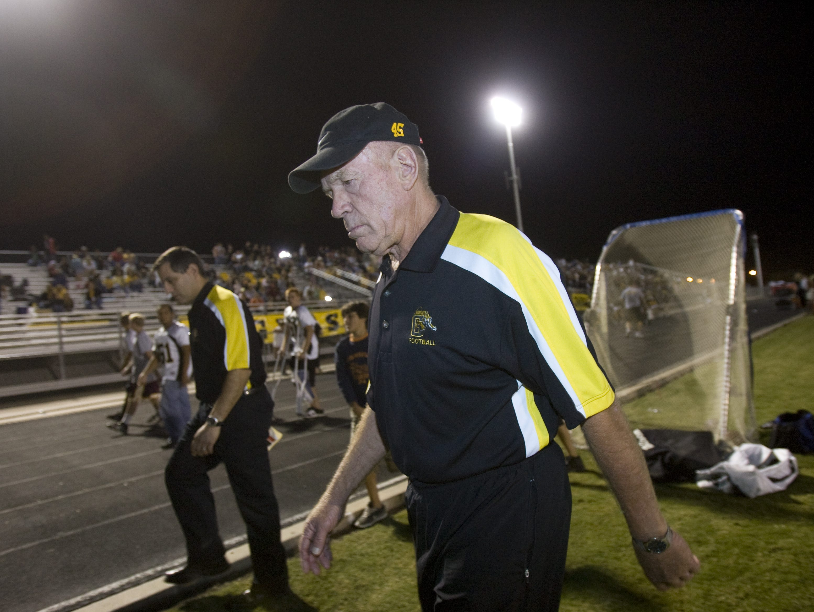 Gilbert coach Jesse Parker walks off the field at the half during a game against Highland in 2008.