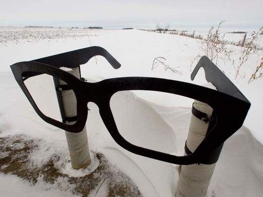 A giant pair of Buddy Holly eyeglasses marks the roadside spot that leads to the crash site north of Clear Lake.