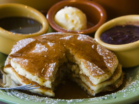 The signature lemon ricotta pancakes from Wildflower Bread Company are made with ricotta cheese and zesty lemon and served with a berry compote, sweet creamy butter and hot maple syrup.