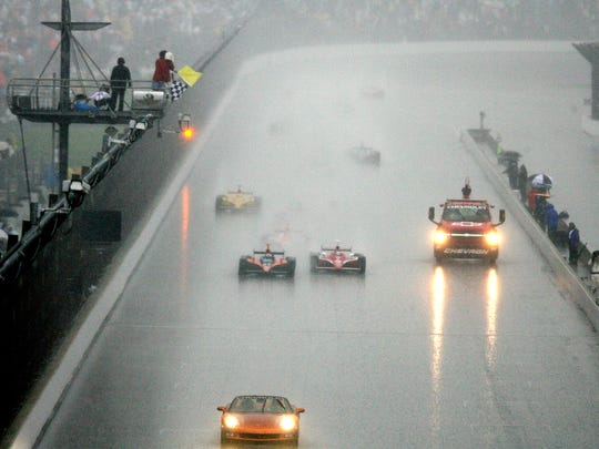 Checkered and yellow flags wave as Dario Franchitti (left), winner of the 91st running of the Indianapolis 500, crosses the finish line under caution as the race ended after 166 of the 200 laps when a heavy downpour hit the track on May 27, 2007.