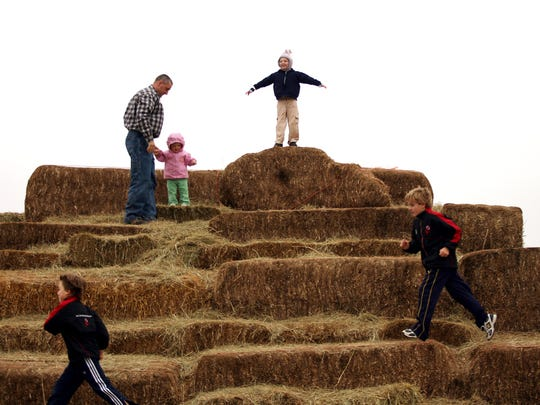 Visitors climb the hay pyramid at Alstede Farms in