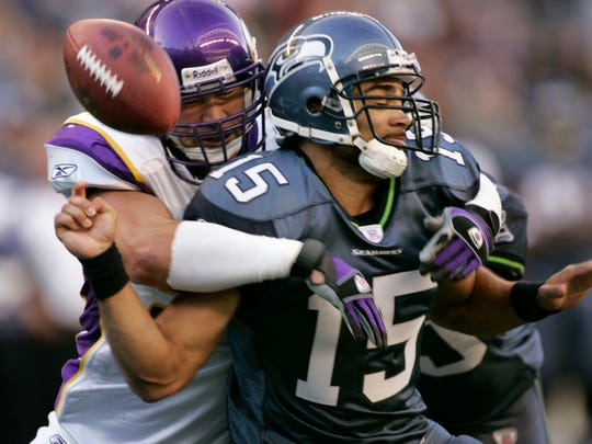 Seattle Seahawks quarterback Seneca Wallace (15) has the ball knocked loose by Minnesota Vikings' Ben Leber in the fourth quarter in a football game Sunday, Oct. 22, 2006, in Seattle. The Vikings recovered in the endzone for a touchdown. Minnesota won, 31-13.  (AP Photo/Elaine Thompson)