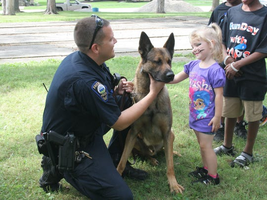 """Aurora Carrothers pets K-9 Woody and talks to Fremont Officer Pete Bush. The Fremont Police Department and the Sandusky County Sheriff's Office sponsored a """"Fun Day with Cops"""" event, Sunday at Birchard Park."""